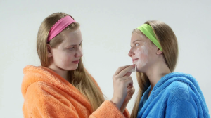 teen-skin-care-treatment-teenage-girls-with-facial-cream-masks-on-white-background-girl-wiping-off-mask-on-the-face-of-her-girlfriend_rwthibc9_thumbnail-full01